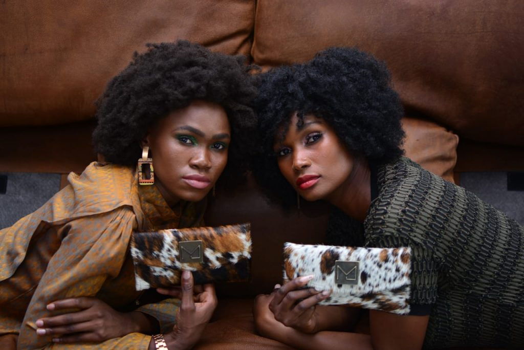 2 Mabotho models on a couch with handbags